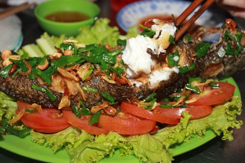 Nhúng miếng bánh tráng, giẽ thịt cá lóc và gắp một miếng bún, rau sống đặt lên miếng bánh tráng cuốn lại chấm vào chén nước chấm, đưa lên miệng.
