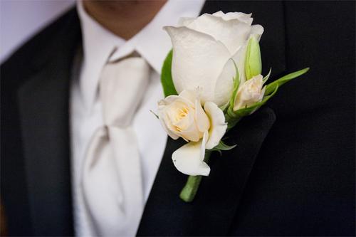 Để hợp tông với cô dâu, chú rể cũng nên chọn hoa cài áo từ hoa hồng trắng.