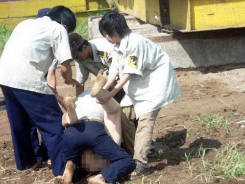 Con gái bà Lài là chị Hồ Nguyên Thủy (33 tuổi) cũng lột hết quần áo để phản đối cũng bị nhóm vệ sĩ lao đến trấn áp. Trong ảnh là một vệ sĩ đè ngay trên người chị Thủy.