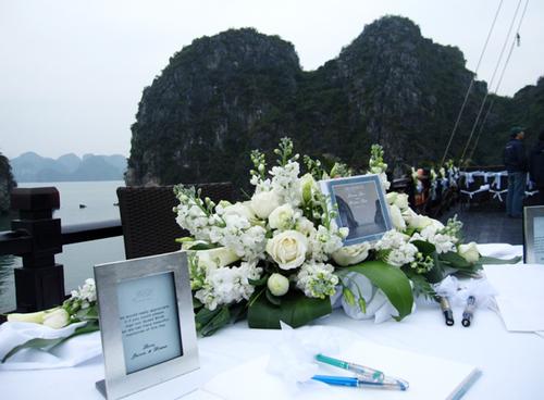 Bàn đón tiếp được trang trí trang nhã với hoa hồng trắng tinh khôi, hoa phi yến dịu dàng, khung ảnh kỷ niệm và là nơi bạn bè viết những lời chúc mừng hạnh phúc tới đôi uyên ương.