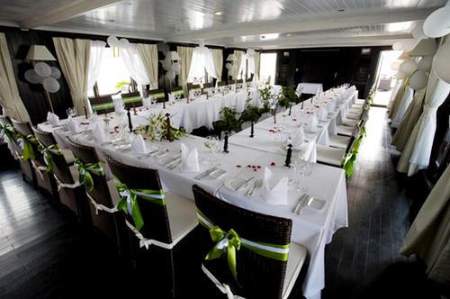 Phần tiệc được tổ chức trong khu vực nhà hàng với tông màu xanh cốm và trắng, đồng nhất với không gian lễ cưới ngoài trời.