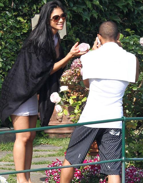 Cặp đôi tình tứ đi dạo và chụp ảnh ở vườn hoa.