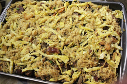 Món xôi ăn kèm thịt gà, lạp xưởng, tôm khô và ruốc, với ít trứng gà thái sợi và mỡ hành.