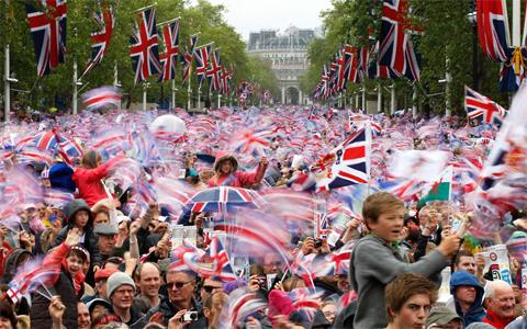 Người dân hân hoan vẫy cờ khi đoàn xe ngựa của hoàng gia đến cung điện Buckingham. Ảnh: AP