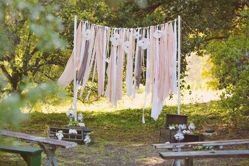 Nếu tổ chức cưới ngoài trời, một tấm backdrop từ các dải lụa sẽ là lựa chọn hợp lý, tạo điểm nhấn mềm mại, tung bay trong gió.