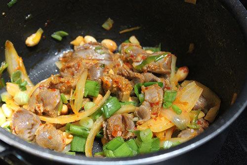 Cuối cùng cho lạc và hành lá thái nhỏ vào, tắt bếp, múc ra đĩa ăn.