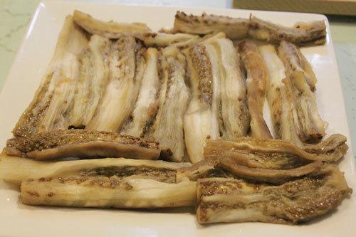 Bổ cà thành những miếng dài xếp vào đĩa, cho thịt lên trên.