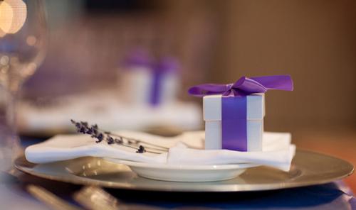 Trên bàn, mỗi vị khách đều được tặng một món quà xinh xắn giữ trong hộp thắt ruy băng tím đáng yêu.