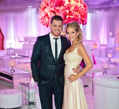 Cô dâu Luisana Lopilato chọn một chiếc váy dạ hội màu vàng kem khéo léo khoe vòng một gợi cảm, còn chú rể Michael Buble đơn giản trong trang phục vest tối màu.