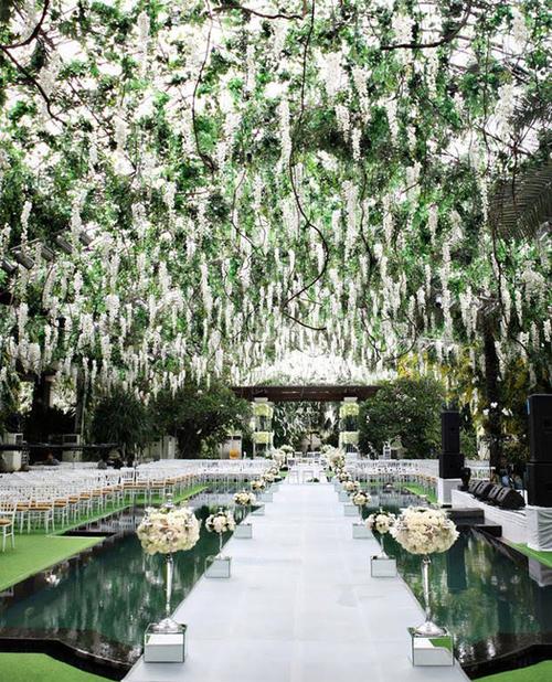 Một không gian sân khấu lộng lẫy nằm bên hồ bơi với dàn hoa đẹp và hai hàng hoa dẫn lối lên sân khấu.