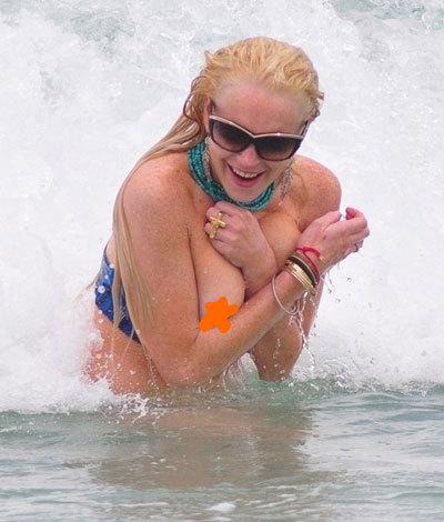 Lindsay Lohan mải vui đùa với sóng khiến cô lộ cả hai gò bồng đảo.