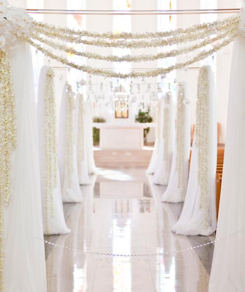 Trong không gian nhà thờ, đôi uyên ương dựng một chiếc cổng hoa lớn màu trắng để tô điểm cho lối dẫn lên thánh đường.