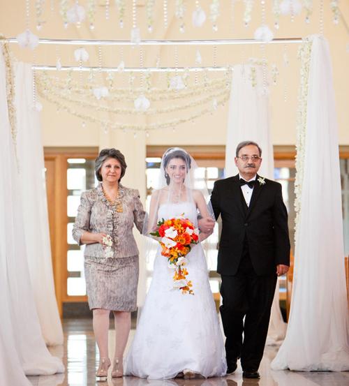 Giữa không gian trắng trang nghiêm của nhà thờ, cô dâu với bó hoa cam rực rỡ trở nên vô cùng nổi bật.