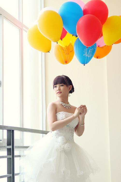 Cô dâu lộng lẫy trong chiếc váy cưới và nổi bật cùng chùm bóng trên nền căn phòng trắng.