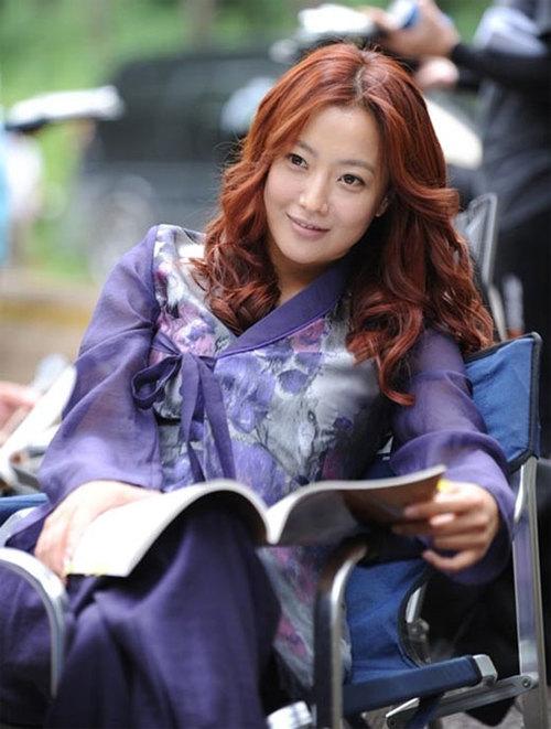 Kim Hee Sun trên trường quay, khi cô đang tranh thủ đọc kịch bản.