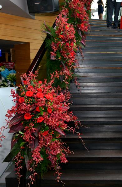 Tiệc cưới của Đoan Trang bắt đầu từ 16h chiều ngày 30/7 tại quầy bar nằm trên tầng thượng một cao ốc tại TP HCM. Đây là lần đầu, nơi đây tổ chức tiệc cưới. Sau khi đi thang máy lên tầng 26, khách mời bước ra cầu thang bộ được trang trí những lẵng hoa hồng và lan đỏ xen kẽ dọc hai bên cầu thang để lên sảnh tiệc ngoài trời.