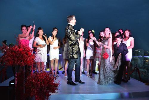 Cô dâu chú rể lên sân khấu chia sẻ về tình yêu và hòa giọng song ca một ca khúc tiếng Anh cùng dàn đồng ca diện trang phục trắng.