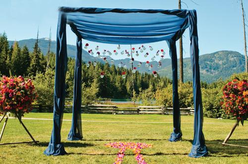 Khu vực lễ thành hôn của đôi uyên ương được tổ chức ngoài trời. Sân khấu là một mái vòm được trang trí bằng lụa xanh, hai bên mái vòm là hai lẵng hoa tông màu nóng.