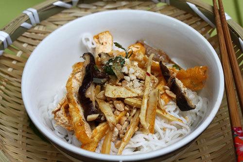 Tô bún chay hấp dẫn với những miếng đậu phụ được chiên vàng óng, bên cạnh là nấm xào, lạc rang làm cho món ăn thêm ngon miệng.