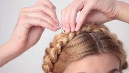 Dùng một chiếc châm để kéo nhẹ lọn tóc tết sang hai bên, mái tóc trông sẽ tự nhiên hơn.