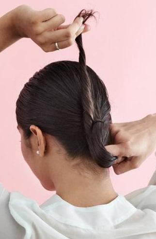 Khi tạo búi tóc, bạn kẹp một ngón tay vào giữa để tạo khoảng trống. Sau đó, luồn đuôi tóc qua khoảng trống này.