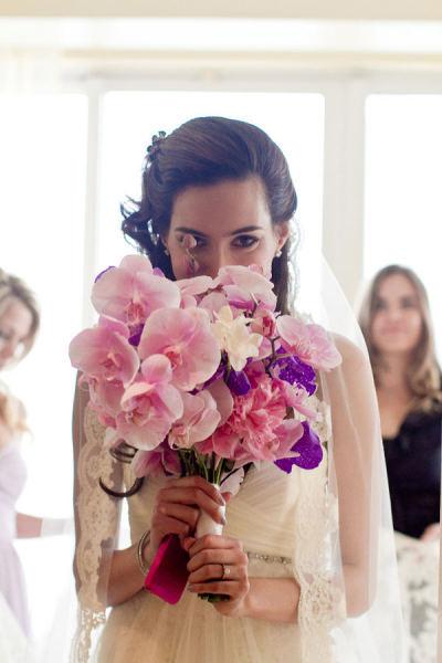 Cô dâu dịu dàng với bó hoa lan tím hồng.