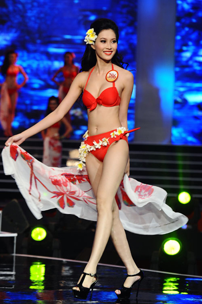 Hoa hậu Việt Nam 2012 Đặng Thu Thảo vừa cài hoa lên mái tóc vừa khéo léo quấn vòng hoa quanh hông để tạo điểm nhấn cho phần thi bikini của mình.
