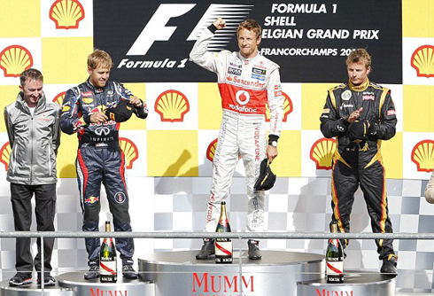: Button celebrated on the podium after winning ahead of second placed Red Bull driver Sebastian Vettel and third placed Lotus driver Kimi Raikkonen