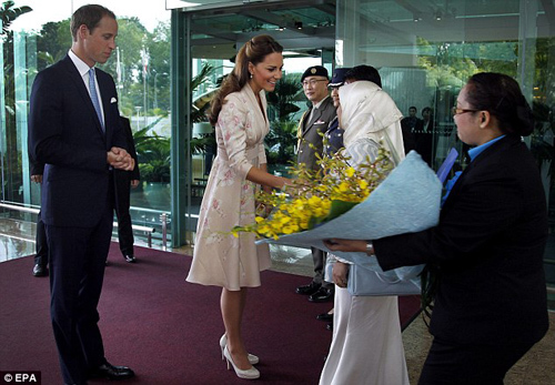 Britain's Prince William looks on as his wife Catherine, Duchess of Cambridge, receives flowers upon their arrival at the VIP terminal of Changi International Airport in Singapore