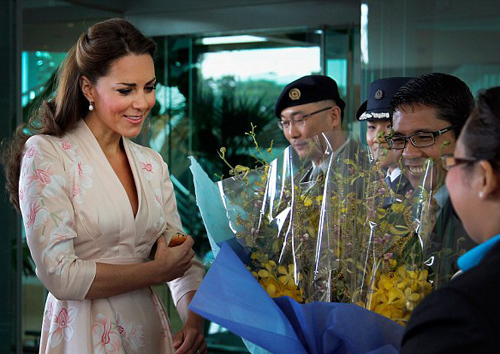 The Duchess of Cambridge being presented with a huge bouquet of yellow flowers by the wife, Sadiah Bte Shahal, of the Senior Parliamentary Secretary for the Ministry of Defence Maliki Osman