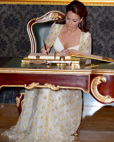 The Duchess of Cambridge signs the visitors' book, left, before the couple were led into the heavily-brocaded Seri Mahkota Hall or audience room