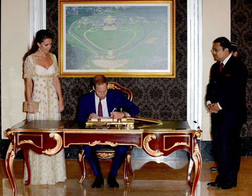 The Duke and Duchess of Cambridge sign a visitors book before entering the Istana Negara, in Kuala Lumpur
