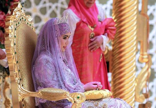 Màu sắc váy cưới của cô dâu khác biệt hoàn toàn với trang phục của tất cả khách mời trong phòng cưới. Màu tím cũng làm cô dâu nổi bật trên nền của ngai vàng.