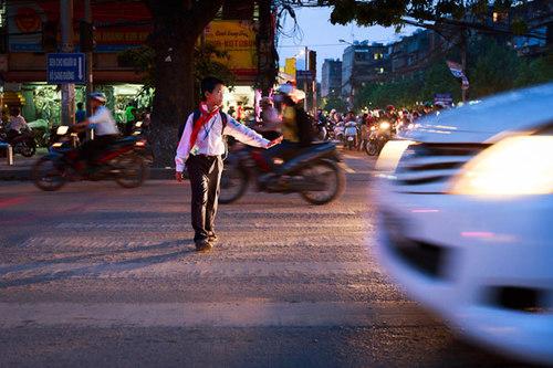 Một em học sinh trên đường đi học về. Dù đã đi đúng vạch sơn kẻ dành cho người đi bộ nhưng cậu bé không dùng nút bấm đèn cho người đi bộ ngay gần đó.