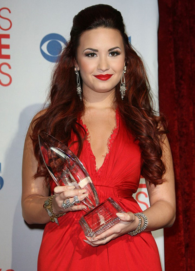 Cùng ngắm qua hình ảnh của Demi trong lễ trao giải People Choice Award năm 2012 vừa qua. Phần tóc mái được đánh phồng và kẹp gọn phía sau đầu. Phần còn lại được thả tự nhiên dọc sau gáy, với những lọn tóc xoăn nhẹ nhàng, hết sức quyến rũ.