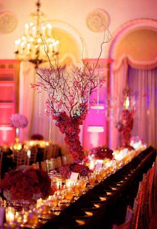 Với mỗi kiểu bàn tiệc, trang trí hoa lại khác nhau. Với bàn dài, nhà thiết kế hoa sử dụng mẫu hoa cao kết hợp cùng cành khô và dải pha lê dài.