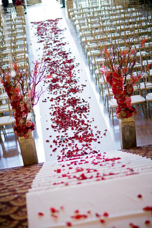 Nơi tổ chức lễ thành hôn được trang trí đơn giản, chỉ có hai trụ hoa lớn và thảm cánh hoa hồng điểm nhấn nổi bật và thu hút sự chú ý của các vị khách mời.