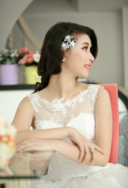 Mái tóc uốn nhẹ nhàng và một chiếc nơ cài tóc là đủ để làm cô dâu nổi bật với tông cam rực rỡ.