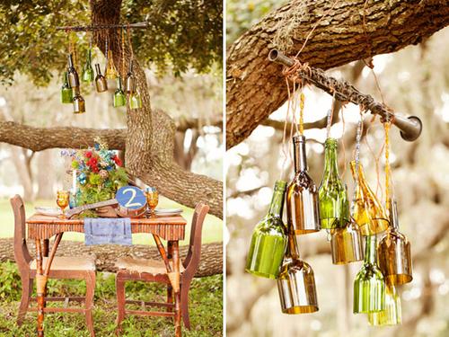 Bàn tiệc được thiết kế bằng gỗ, trên bàn là cụm hoa ngẫu hứng và trên cao là bộ đèn chùm được thiết kế đặc biệt từ các chai thủy tinh màu.
