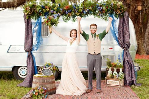 Khác hẳn với những đám cưới thường đặt hoa lẵng ở hai bên cổng hoa, đôi uyên ương sử dụng thùng rượu vang cũ, hoa, sách và những chiếc lọ hoa đáng yêu làm phụ kiện trang trí.