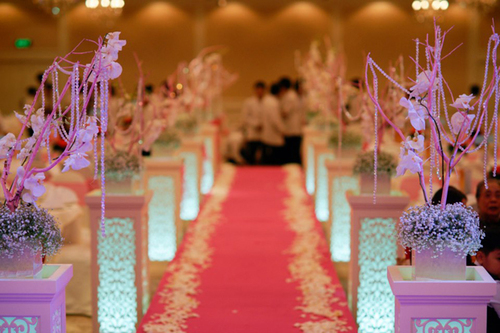 Thay vì trải thảm đỏ, thảm dẫn lối lên sân khấu có màu hồng, phù họp với tông màu chủ đạo của đám cưới.