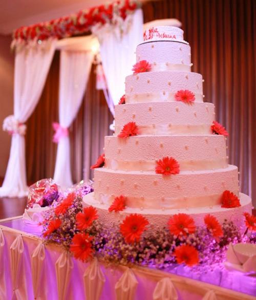 Bánh cưới nhiều tầng được trang điểm ngọt ngào với hoa đồng tiền và baby ở chân bánh.
