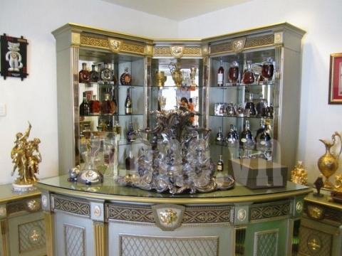 Tủ rượu được bài trí tại góc phòng, với sự hiện diện của nhiều loại rượu quý được sắp xếp theo nhãn hiệu.