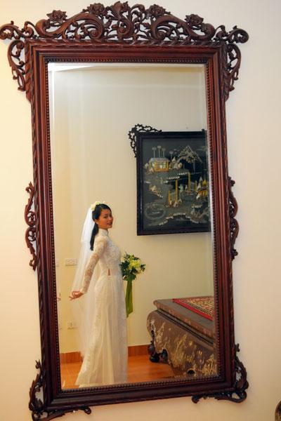 Không chọn lại chiếc áo dài đỏ trong lễ cưới tại chùa, Hải Yến mặc áo ren trắng trong đám cưới tại Bắc Ninh. Cô cũng chuẩn bị hoa cưới, khăn voan dài để tô điểm thêm cho nhan sắc dịu dàng, đằm thắm.