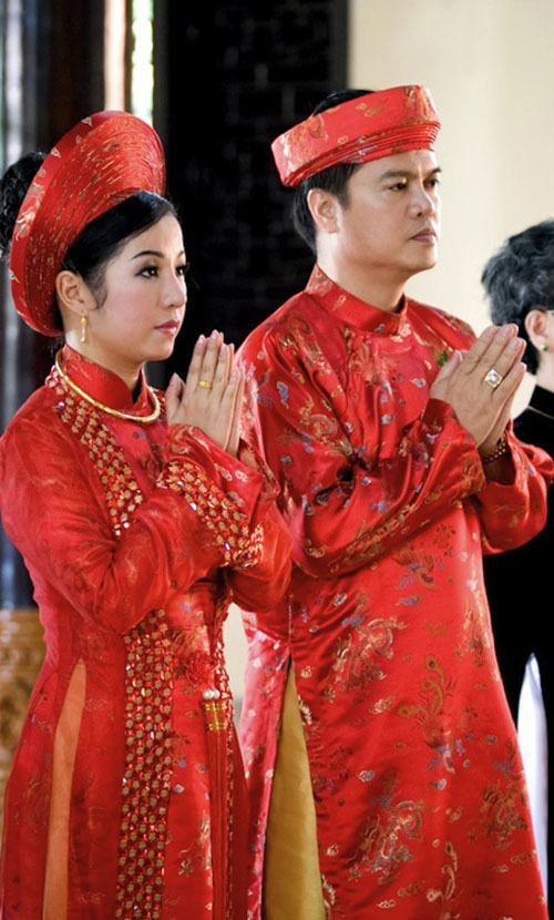 Diễn viên hài Thúy Nga mặc áo dài đỏ họa tiết rồng, phượng và những họa tiết truyền thống của đám cưới Việt Nam.