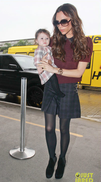 Victoria passed through LAX airport in a maroon Miu Miu jumper and plaid skirt, while Harper was dressed in a cosy grey coat.