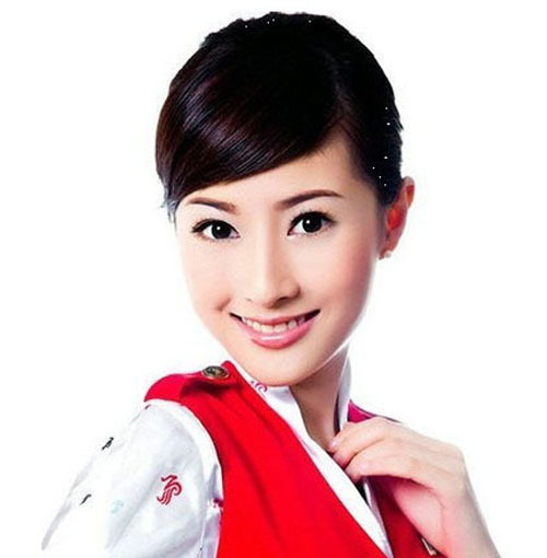 """Sun Qing is the brand spokeswoman for Shenzhen Airlines. She resembles Michelle Monique Reis, a gorgeous Hong Kong actress. However, Sun's most attractive feature is not her face, but her bright smile. Her smile is reminiscent of early morning sunshine sprinkled above the sea. One of her passengers once sent her a silk scarf (as a gift) and gushed that her smile could help relieve the most dreadful fatigue. """"My work makes me mature, however, I have to work harder,"""" she said. Her passion for her job is the reason why she is so successful and popular."""