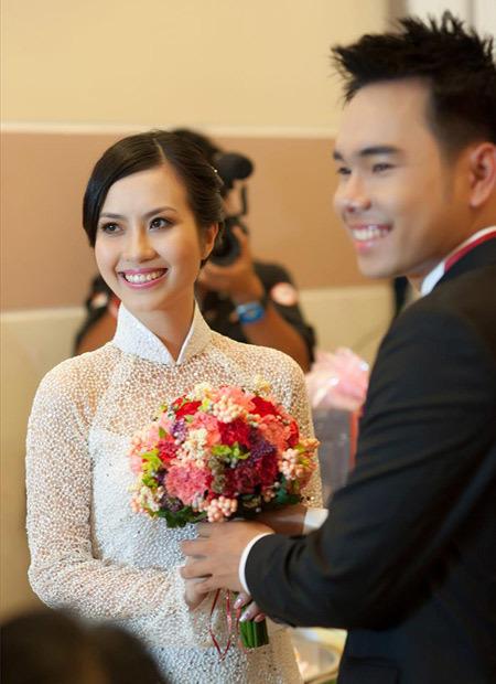 Trên nền áo dài màu trắng, bó hoa cưới kết từ cẩm chướng nhiều màu thực sự làm cô dâu nổi bật hơn.