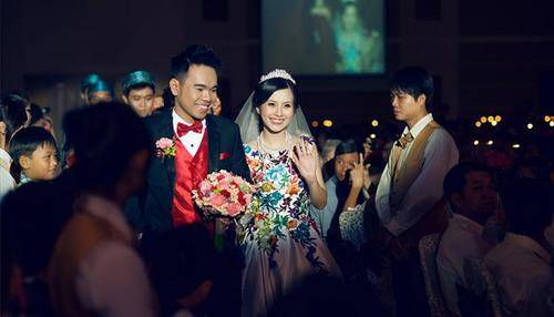 Cô dâu chú rể rực rỡ với các tông màu bắt mắt, nắm tay nhau bước vào tiệc cưới.