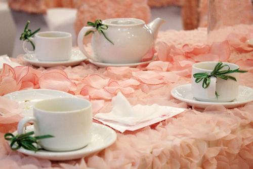Trên bàn, những bộ ấm chén được làm điệu với nơ xanh màu lá cây, tạo thêm điểm nhấn nhỏ nhưng thú vị.